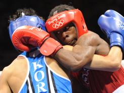 Rau'shee Warren (right) fights Korea's Oksung Lee in a flyweight preliminary bout at the Beijing Olympics. Warren lost by a one-point decision.