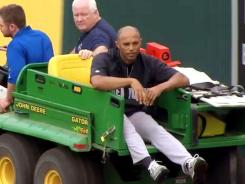 Yankees' Mariano Rivera, right, is being carted off the field after twisting his right knee shagging fly balls.