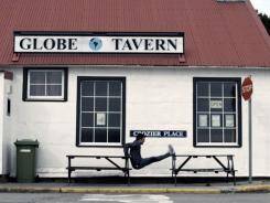 In this frame grab from a TV advertisement released by the Argentine Presidential Office, an Argentine Olympic field hockey player Fernando Zylberberg exercises in front of the Globe Tavern in Stanley, Falkland Islands.
