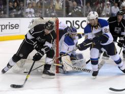 Kings center Brad Richardson looks for an opening behind the Blues goalie Brian Elliott (1) and defenseman Keiven Shattenkirk (22).