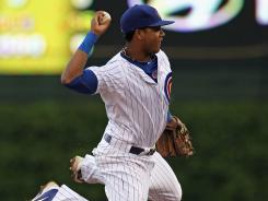 Starlin Castro leaps over Tony Gwynn as he throws to first to turn a double play against the Dodgers on Sunday. Castro drove in two runs as the Cubs prevailed in extra innings.