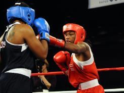 Claressa Shields (red) throws a punch at Tika Hemingway (blue) during their middleweight bout at the Women's Olympic Boxing Trial Finals on Feb. 18, 2012.
