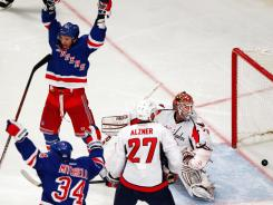 The Rangers' Artem Anisimov, top left, and John Mitchell (34) celebrate as teammate Marc Staal (not pictured) scores the game-winning goal past Capitals goalie Braden Holtby during overtime.