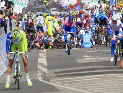 Sprint favorite Mark Cavendish (C, red jersey) and overall leader Taylor Phinney (L, pink jersey) sit on the ground 100 meters from the finish line after falling at the third stage of the Giro d'Italia.