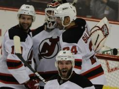 New Jersey Devils teammates mob goalie Martin Brodeur after beating the Philadelphia Flyers 3-1 Tuesday.