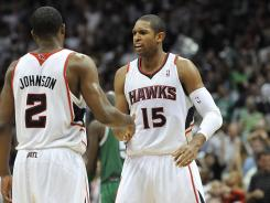 Atlanta Hawks shooting guard Joe Johnson (2) and center Al Horford (15) celebrate defeating the Boston Celtics in Game 5 on Tuesday.