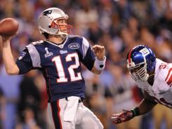New England Patriots quarterback Tom Brady, left, passes under pressure from New York Giants defensive end Justin Tuck during Super Bowl XLVI.