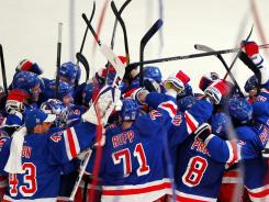 New York Rangers players celebrate after their Game 5 overtime win on Monday.