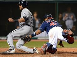 Alex Rios, who tripled home the eventual game-winning run earlier in the inning, slides safely past Indians catcher Carlos Santana in the top of the 10th Tuesday night to make it 5-3 White Sox.