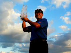 K.J. Choi of South Korea celebrates with the trophy after winning The Players Championship in 2011.