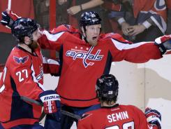 Washington Capitals left wing Jason Chimera (25) celebrates a goal against the New York Rangers with teammates defenseman Karl Alzner (27) and left wing Alexander Semin (28).