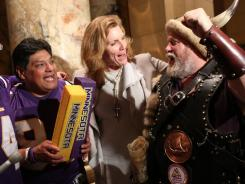 Sen. Julie Rosen, center, celebrates with Vikings fans after the Senate passed a bill for a new $975 million stadium.