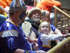 "Minnesota Vikings fan Hannah Walsh, 5, sits between ""Skolt,"" left, also known as Scott Asplund, and Greg Hanson, who goes by Sir Odin, as the state Senate discussed the Vikings stadium bill Tuesday."