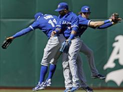 The Blue Jays' Rajai Davis, left, Jose Bautista and Colby Rasmus celebrate after their 5-2 win over the Athletics on Wednesday.