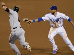 The Giants' Brett Pill tries to avoid a tag from Dodgers first baseman James Loney during their game in Los Angeles Tuesday night.