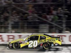 Joey Logano crosses the finish line first in his Joe Gibbs Racing Toyota on Friday night in Darlington, S.C.