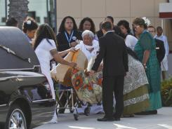 Junior Seau's family helps spread a traditional Samoan cover over the cart which moved Seau's casket into Calvary Chapel for his funeral viewing on May 10, 2012, in Oceanside, Calif.