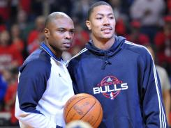 Injured Chicago Bulls guard Derrick Rose, right, had surgery Saturday to repair his torn knee ligament.