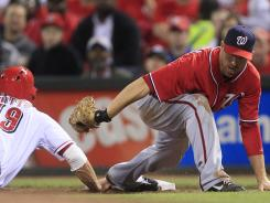 Reds first baseman Joey Votto is doubled off first base by Nationals first baseman Adam LaRoche in the sixth inning of their game Saturday in Cincinnati.