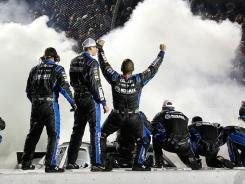 Jimmie Johnson's crew celebrates while the No. 48 Chevrolet burns out after winning at Darlington Raceway.