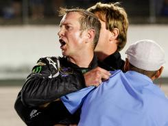 Kurt Busch is held back by team members after a postrace scuffle involving his team and Ryan Newman's.