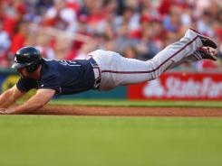 Braves second baseman Dan Uggla slides safely into third base against the Cardinals on Saturday.