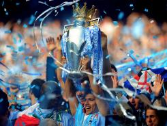 Manchester City's Sergio Aguero celebrates with the trophy after City won the English Premier League championship. Aguero scored the winning goal in stoppage time to give City a 3-2 victory over Queens Park Rangers.