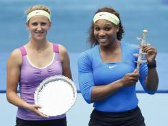 Serena Williams, right, holds the winner's trophy after defeating Victoria Azarenka of Belarus in the Madrid Open final on Sunday.
