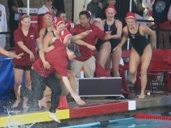 Stanford coach John Tanner heads for a celebratory dip in the pool after his third national title.