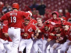Joey Votto heads toward his teammates at home plate after hitting a walk-off grand slam against the Nationals Sunday. It was one of Votto's three home runs on the day.