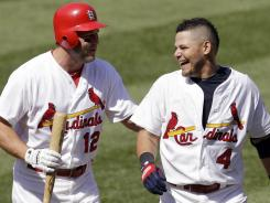 Cardinals' Yadier Molina, right, laughs as he is congratulated by Lance Berkman after hitting a ninth-inning game-winning single.