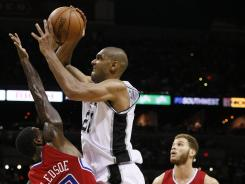 San Antonio forward Tim Duncan (21) gets fouled while shooting against Los Angeles guard Eric Bledsoe (12) during the second half in the Spurs' Game 1 win over the Clippers on Tuesday at San Antonio.