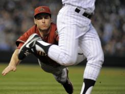 Diamondbacks first baseman Paul Goldschmidt dives but misses Rockies pitcher Jamie Moyer who beat out an infied hit that scored two runs.