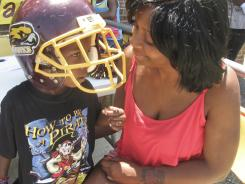 Isha Mackall, 24, is shown with her son, Riyan Snowden, 5, after registering him to play youth football in Annapolis, Md., on May 18.