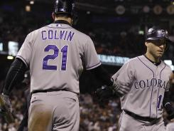 Colorado Rockies' Marco Scutaro, right, is congratulated by Tyler Colvin after after hitting a solo home run off of San Francisco Giants pitcher Santiago Casilla during the ninth inning of the Rockies' 5-4 win over the Giants on Tuesday night.