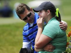 Churchill athletic director Kelly Bokn, left, comforts Caroline Inglis after Inglis' disqualification at the Class 5A state high school championship girls' golf tournament.