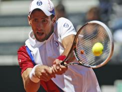 Novak Djokovic of Serbia eyes a backhand during his three-set victory Thursday against Juan Monaco of Argentina.