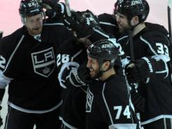 Los Angeles Kings players congratulate Dwight King (74) on his go-ahead goal in the third period.