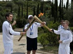 The first torch bearer Spyros Gianniotis (left) hands over the Olympic flame to British boxer Alexandros Lucas during the torch relay on May 10 after the lighting ceremony in ancient Olympia the sanctuary where the Olympic Games were born.
