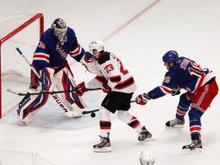 New Jersey winger David Clarkson (23) takes a shot on Henrik Lundqvist as Marc Staal defends during Game 2 two of the Devils-Rangers series.
