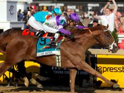 Mario Gutierrez, aboard I'll Have Another, pulls past Mike Smith, aboard Bodemeister, to win the 137th running of the Preakness Stakes at Pimlico Race Course in Baltimore.