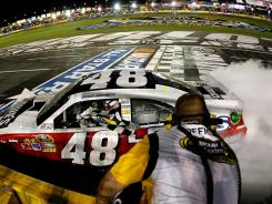 Jimmie Johnson celebrates his third All-Star Race win with the checkered flag on Saturday night at Charlotte Motor Speedway.
