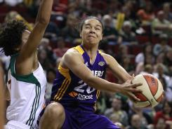 Seattle Storm's Tanisha Wright, left, defends Los Angeles Sparks' Kristi Toliver on a leaping drive in the first half of the Sparks' season-opening win on Friday at Seattle.