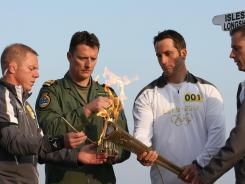 British sailor Ben Ainslie (second from right), the first torchbearer, lights the Olympic torch from the Olympic flame at Land's End, the southwesterly tip of England. The flame arrived in Britain from Greece on Friday and was flown to Land's End on Saturday by a Royal Navy helicopter.