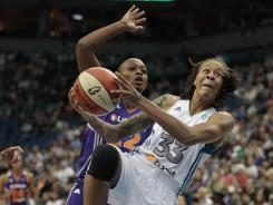 Lynx guard Seimone Augustus, right, drives past former teammate Charde Houston to score two of her 19 points against the Mercury.