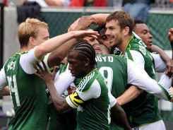 Portland Timbers players teammates celebrate with Eric Brunner, right, after he scored in the first half against the Chicago Fire on Sunday. The goal snapped a 446-minute scoring drought for the Timbers.