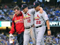 St. Louis Cardinals first baseman Lance Berkman (12) is helped off the field Saturday by manager Mike Matheny (22) and the team trainer after suffering a knee injury. Berkman was placed on the 15-day DL on Sunday.