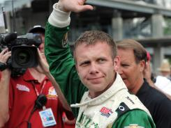 Driver Ed Carpenter, the last driver to qualify for the Indianapolis 500, waves to the fans during Bump Day.