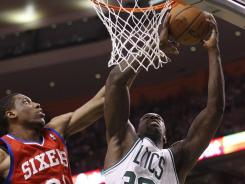 Boston Celtics power forward Brandon Bass (30) takes a shot while being guarded by Philadelphia 76ers forward Thaddeus Young (21) in the third quarter of Game 5 on Monday in Boston.