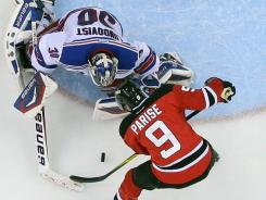 New Jersey Devils left wing Zach Parise scores against New York Rangers goalie Henrik Lundqvist during the third period of Game 4.